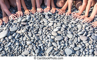 The hands of many children form a semicircle on the beach.