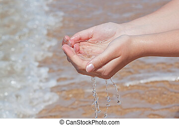 The hands take water into the sea. On the beach.