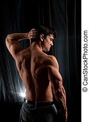 The handsome man flexes his back