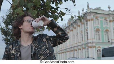 The handsome men is waiting someone, drinks coffee and looks in phone, he is dressed in a military jacket and jeans, State Hermitage museum is on background