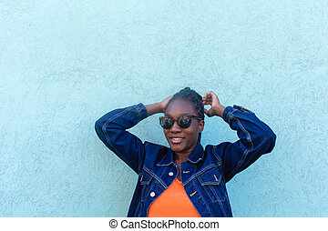 happy African-American woman against the blue wall