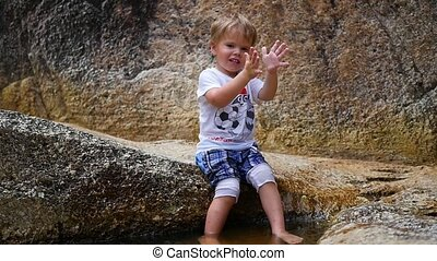 the happy child is sitting on the rocks and plays