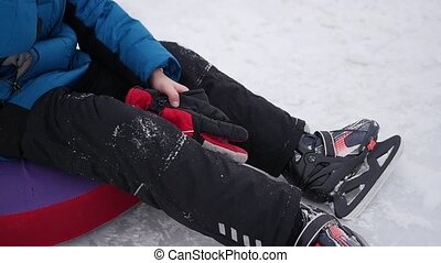 the happy child sits resting and smiling on the ice rink in...