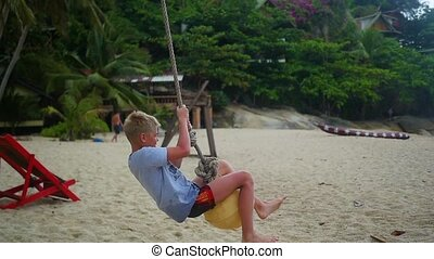 The happy child swinging on a swing on the beach