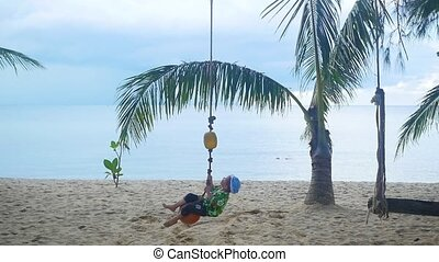 The happy child swinging on a swing on the beach. Tropical island