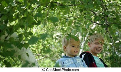 happy children swinging on the branch of a birch
