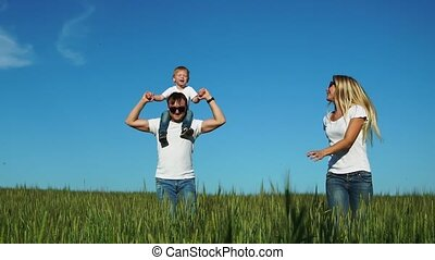 The happy family runs and smiles in the field with their son laughing and holding hands. Son sitting on the lash