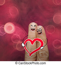 the happy finger couple in love with painted smiley and hold hea