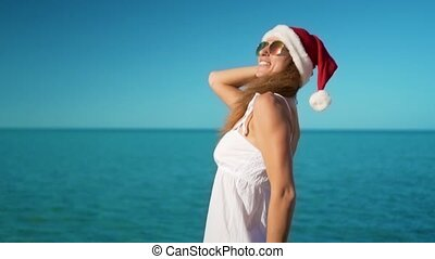 The happy girl in santa claus hat rejoices at sea
