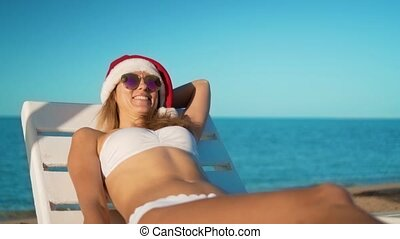 The happy girl in santa claus hat sunbathes on a lounger