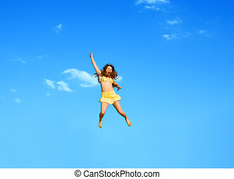happy jumping girl on a background of the blue sky