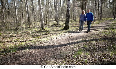 the happy man and the woman goes on a path, talk and laugh, in park in the early spring