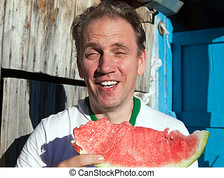 the happy man with a piece of a water-melon