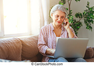 happy old woman senior working at computer laptop at home
