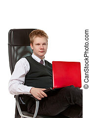 The happy schoolboy in office armchair, with the laptop