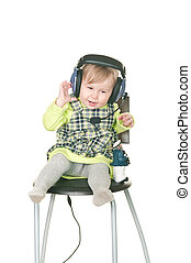 The happy small child sits on a chair in headset ear-phones with a microphone. Isolated on white background