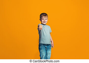 The happy teen boy pointing to you, half length closeup portrait on orange background.