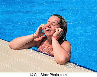 The happy young girl in a swimming pool