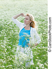 The happy young woman in the field of white wild flowers
