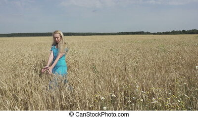 The happy young woman with a long fair hair and in a blue dress goes across the field of ripe wheat to sunny summer day