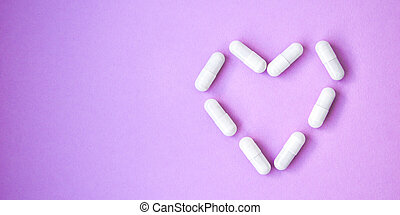 The heart made of tablets and pills on purple background. copy space for text.