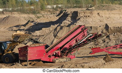 The heavy tractor works in a sand quarry. Quarry sand with a...