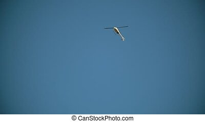 The helicopter flies through the blue sky view from the...