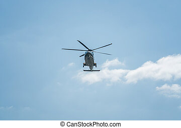 The helicopter is flying in the sky