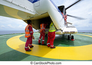 The helideck crew are loading baggage into the cargo ramp of helicopter at oil rig platform