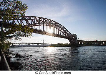The Hell Gate Bridge and the Triborough bridge over the river with blue sky, Astoria park, New York