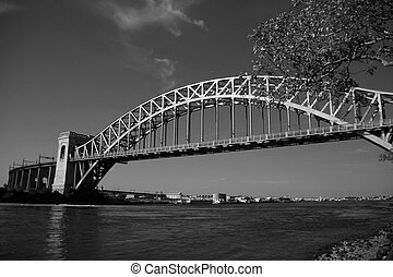 The Hell Gate Bridge over the river and branches in black and white style, New York