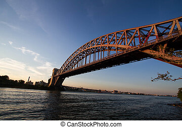 The Hell Gate Bridge over the river with sunset sky, New York