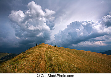The hill in the mountains on the background of dramatic sky and storm clouds
