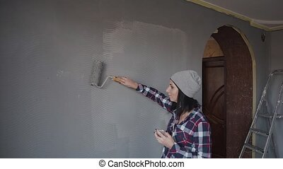 The hipster girl listens to music in the headphones from the phone and paints the walls in his room. A woman paints walls with a roller gray paint. Repair at home