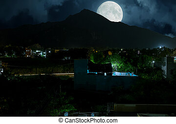 The holy mountain Arunachala with full moon in India at night