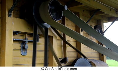 The home made old time noisy farm machine and the wheels in...