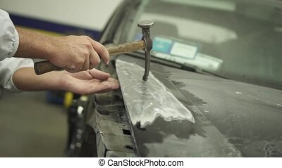 The hood of the car is worked with a hammer