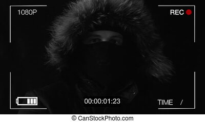 the hooded man in a mask threatens with the gun,black...