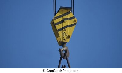 The hook of the elevating crane on blue background industry...