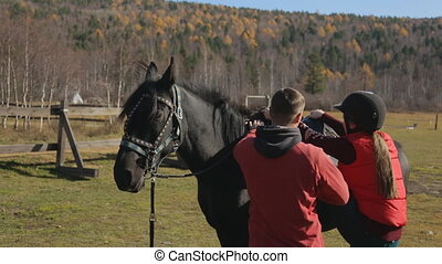 The horse riding trainer helps the female beginner to mount...