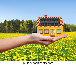 The house in hands.In the background spring landscape.