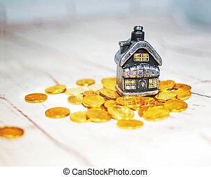The house stands on a pile of coins, the concept of cash savings, loans.