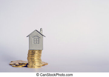 The house symbol on a stack of yellow shiny coins on a light background.