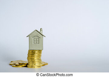 The house symbol on a stack of yellow shiny coins on a light gray blue background.
