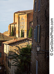 The houses of medieval town in Tuscany, Italy and cypress trees
