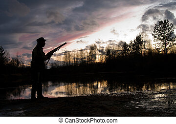 The hunter - Silhouette of the hunter on a background of a...