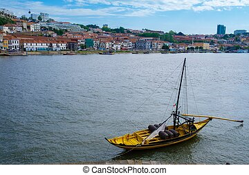 The iconic Rabelo boats, traditional Port wine transport on Douro river, with authentic Ribeira District view, Porto, Portugal.