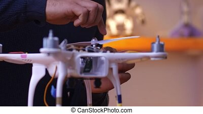 The idea of a distance learning school. Examples of application of skills acquired after education. male hand sets propellers to quadcopter
