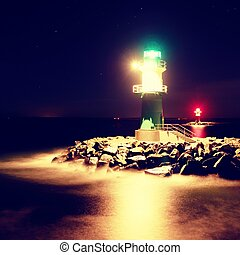 The ighthouse shinning at port gate. Modern light house at the end of stony pier