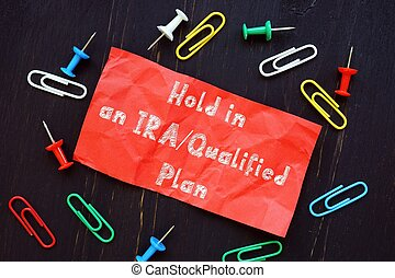 The image contains the inscription Hold in an IRA/Qualified Plan on a notebook sheet